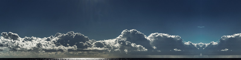 Nephology art. A beautiful panoramic cloudscape scene, with white Cumulonimbus cloud in a mid blue sky.