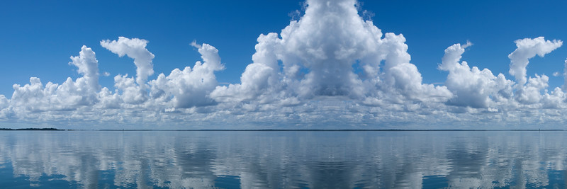 Atmospheric sky art image. White Cumulonimbus cloud in blue sky with ocean water reflections. Australia.