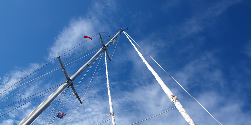 A beautiful sky cloudscape scene, over a yacht mast and rigging, with white Stratocumulus cloud in a light blue sky.