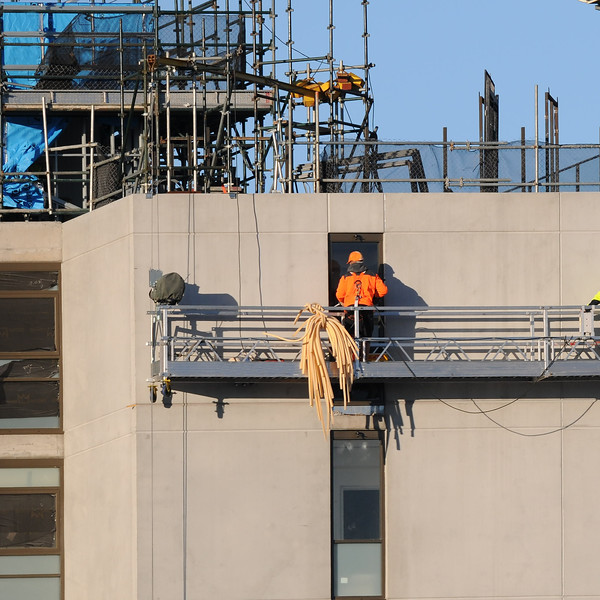 Multistory Unit building under construction at 277 Mann St. Gosford with men working from a platform swing stage on the structure May 12, 2020.