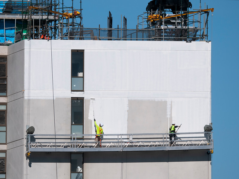 Multistory Unit building under construction at 277 Mann St. Gosford with Painters working from a platform swing stage on the structure May 12, 2020.