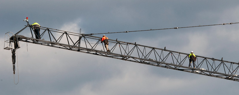 Riggers up high assembling and erecting a construction Tower Crane. May 11, 2019.