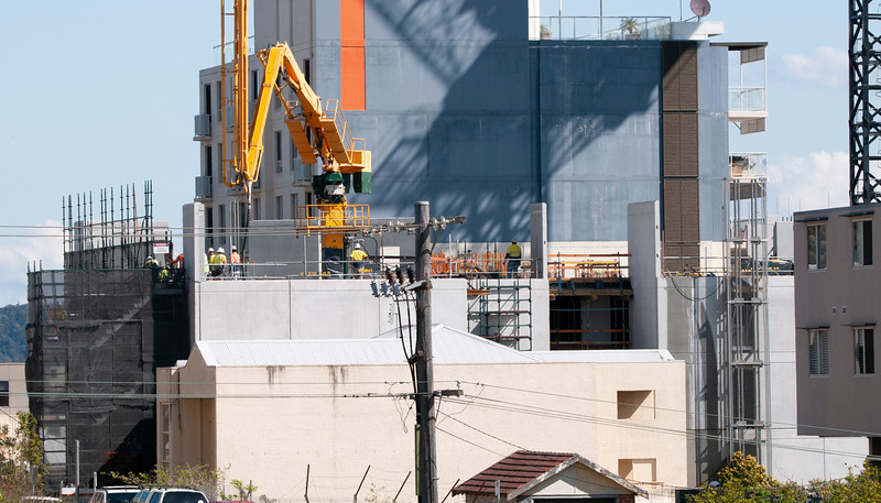 Multistory building under construction with workers, cranes and blue sky. Mann St. Gosford, Australia. September 25, 2019.