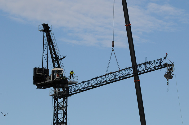 Installing and assembling a heavy duty industrial construction crane on a highrise building site. Australia. May 11, 2019.