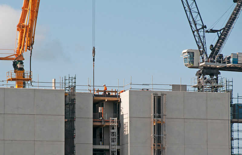 Multistory building under construction. The structure with cranes and blue sky,