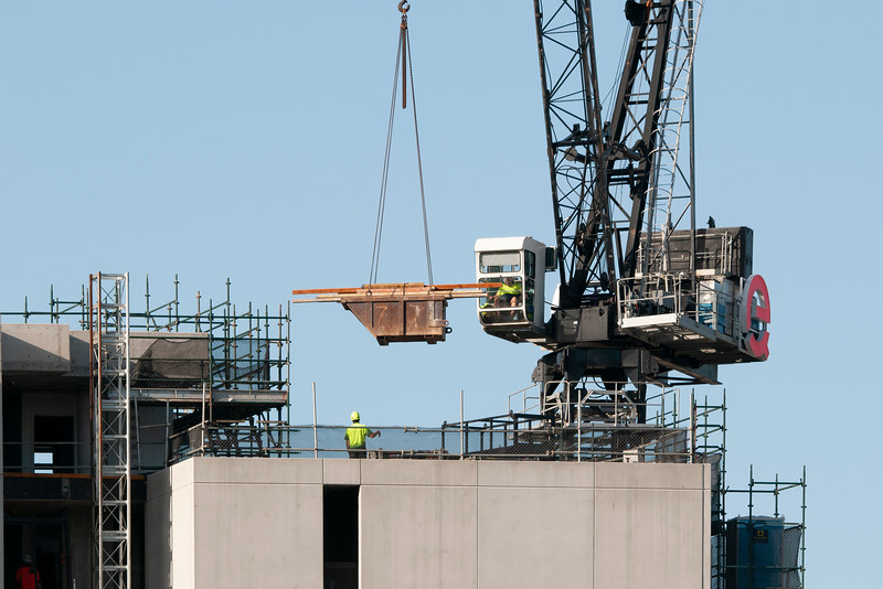 Working Construction Crane loading supplies on Multistory Units.  February 29, 2020. Part of a series.