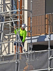 Gosford, NSW, Australia - July 15, 2021: Workman closeup holding a section of scaffolding on the now completed top floors of new social housing.