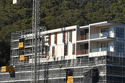 Gosford, NSW, Australia - July 15, 2021: Workmen disassembling safety netting and scaffolding on the now completed top floors of new social housing.