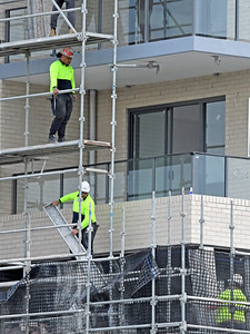 Gosford, NSW, Australia - July 15, 2021: Workmen closeup disassembling scaffolding on the now completed top floors of new social housing.