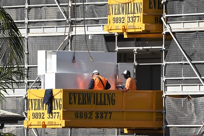 Gosford, NSW, Australia - July 15, 2021: Workmen closeup receiving new building supplies by sky crane on the new social housing.
