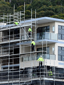 Gosford, NSW, Australia - July 15, 2021: Workmen closup disassembling scaffolding on the now completed top floors of new social housing.