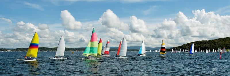 Regatta Panorama. Children Sailing small sailboats (Catamarans) with colourful sails. Australia. Commercial use image.
