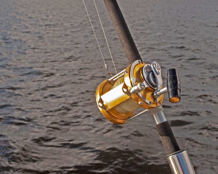 A gold coloured Big Game 50 wide fishing reel closeup in used condition.