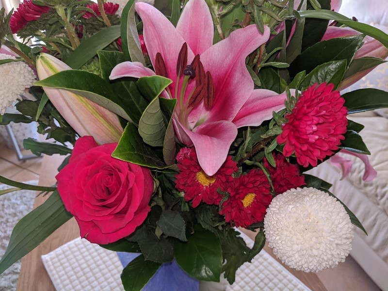 Floral display including Flashpoint pink and white Oriental Trumpet Lily closeup.
