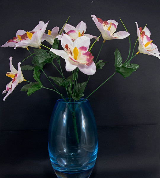 Artificial flower display in a glass vase isolated on a black background.