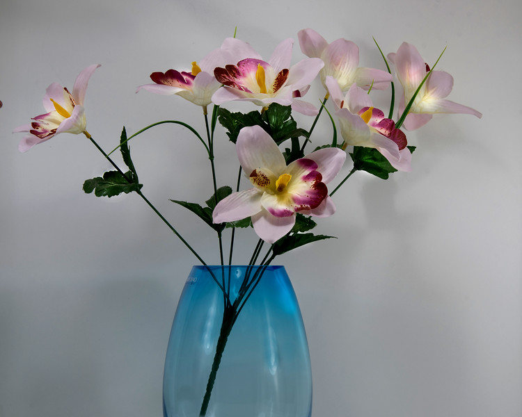 Artificial flower display in a glass vase isolated on a white background.
