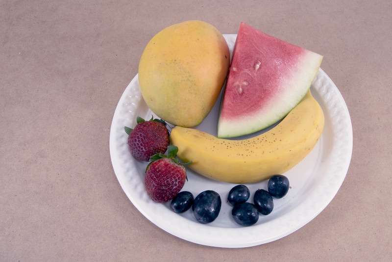 Colourful fresh tropical fruit including strawberry banana on a white plate isolated on a light beige background.