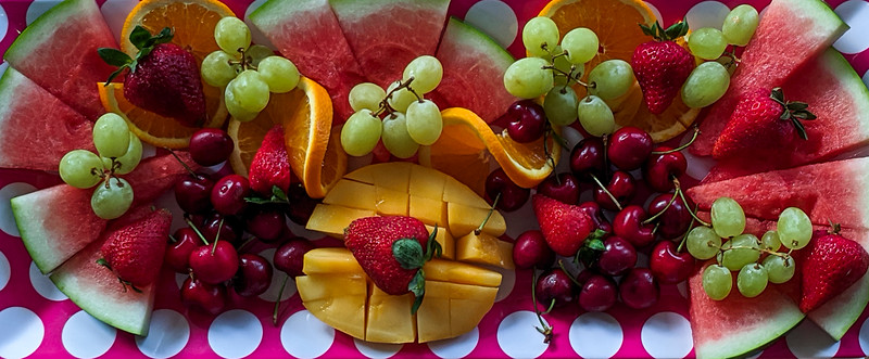 A colourful Christmas breakfast fruit platter on a dining table closeup.