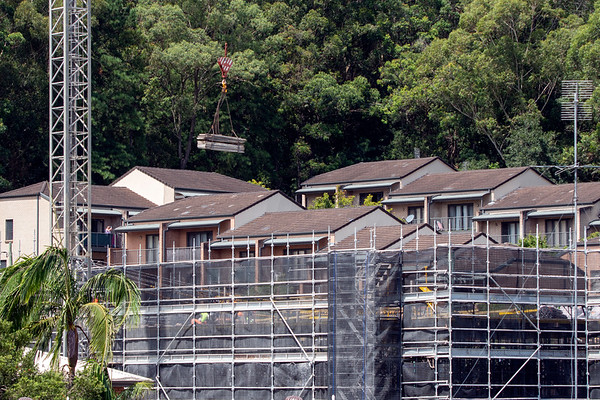 Construction progress with the tower crane delivering materials on new building site with bushland backdrop. Gosford, Australia. March 3, 2021. 56-58 Beane St. Part of a series.