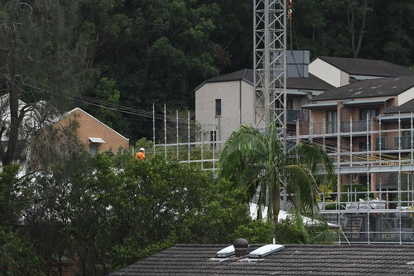 Building landscape with worker assembling scaffolding on new social housing home unit block at 56-58 Beane St. Gosford, Australia. February 27, 2021. Part of a series.