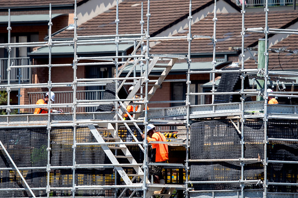 Workers assembling scaffolding on new social housing home unit block at 56-58 Beane St. Gosford, Australia. March 1, 2021. Part of a series.