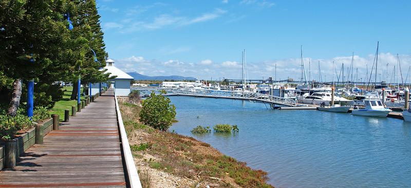 Tropical timber waterfront marina board walk with boats.