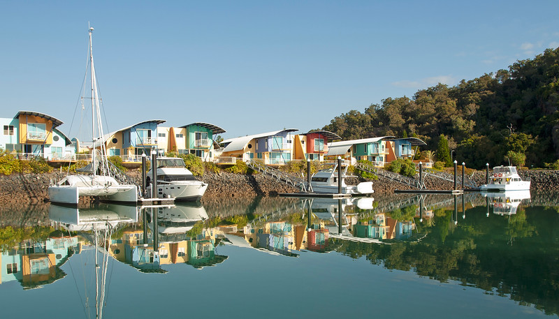 Waterfront marina/dock/resort with boats and clear water reflections.