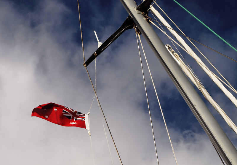 Yacht -Sailboat, mast white cloud blue sky flying a flag