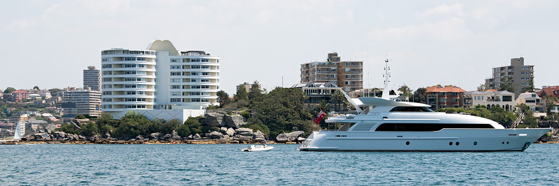 Luxury motor yacht at anchor in North Harbour, with waterfront apartments in the background. Sydney, Australia.
