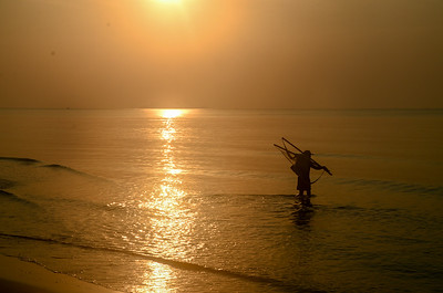 Tropical sunrise seascape with a fisherman, Thailand.
