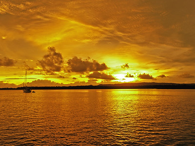 Golden coastal cloudy sunrise seascape.