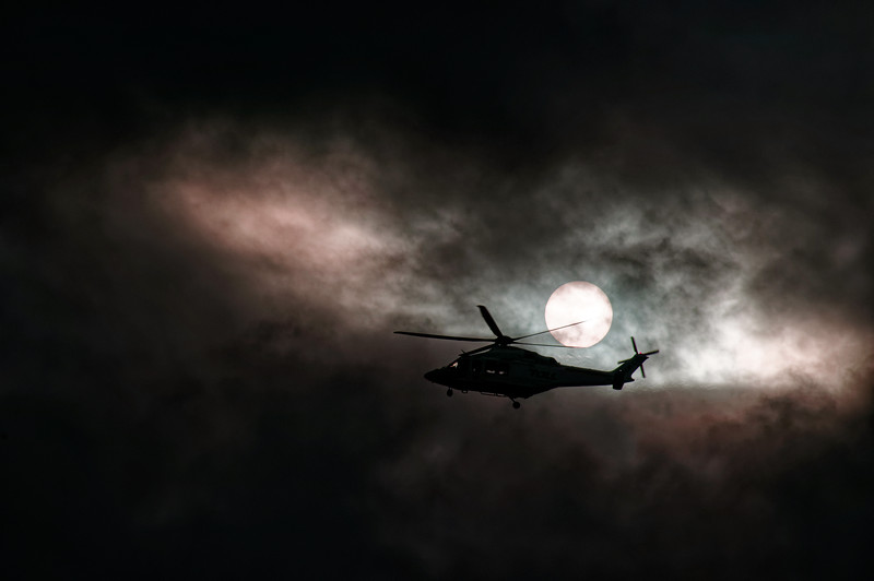 Airborne Helicopter in storm cloud sunset silhouette.