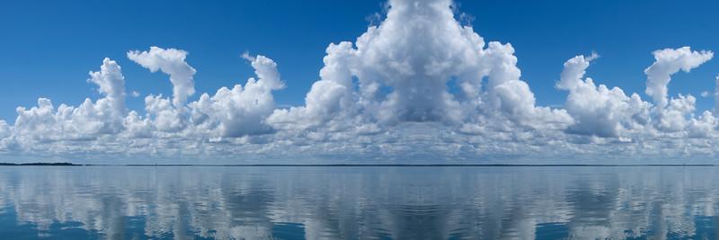Atmospheric sky art image. White Cumulonimbus cloud in blue sky with ocean water reflections. Australia.