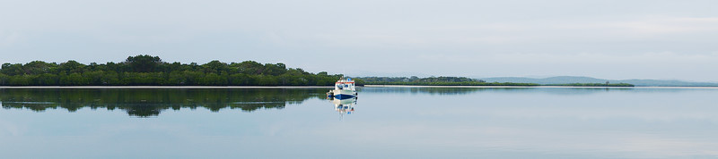 A nautical marine waterscape panorama with boat reflection. Fraser Island.