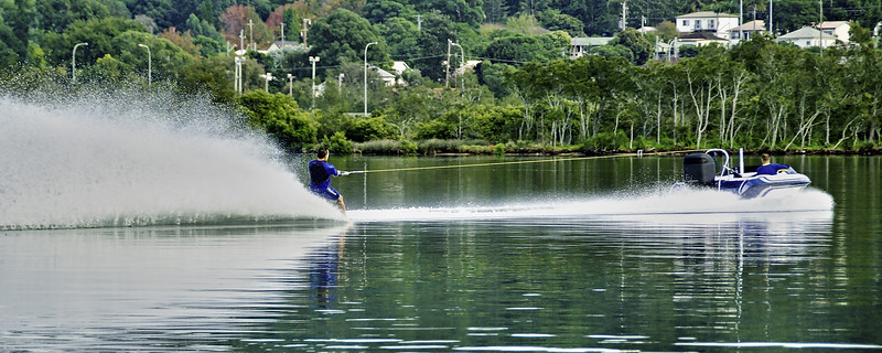 Barefoot water skiier at speed on tranquil water.