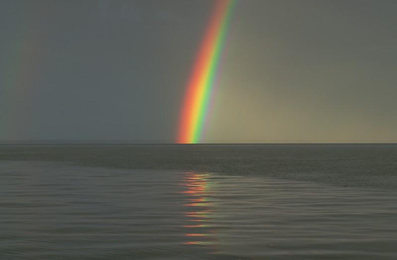 A bold ocean rainbow through bushfire smoke haze.