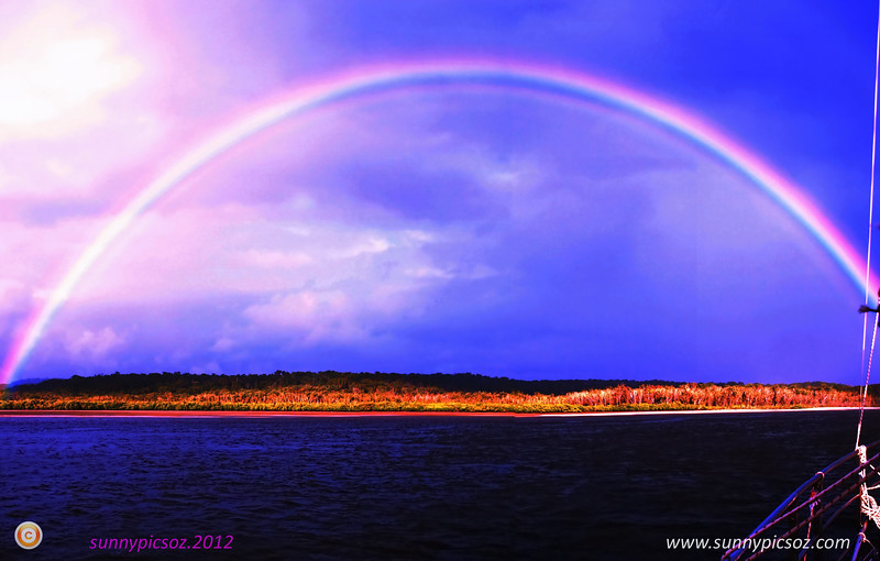 Vibrant glowing full arc tropical rainbow.