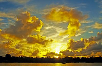 Golden colored coastal sunrise seascape cloudscape.
