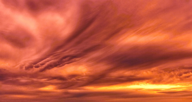 Orange and Gold swirling Surreal  Cirrus Sunset photo over water.