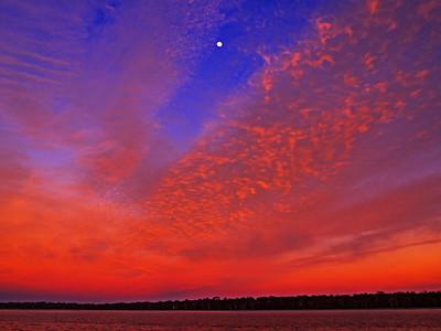 Radient Crimson Cirrus colored coastal sunrise seascape in a vivid blue sky.