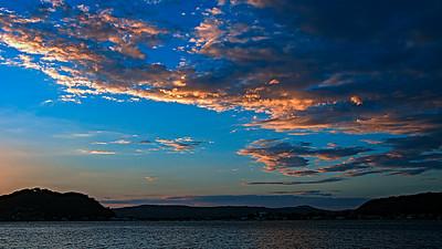 Orange coloured stratucumulus cloud, sunset seascape.