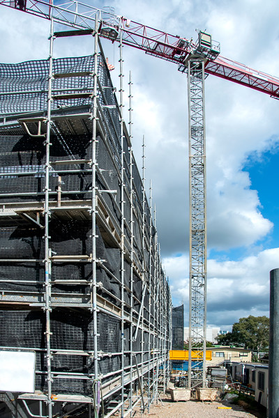 Construction progress on new building site with tower crane and blue sky. Gosford, Australia. March 7, 2021. 56-58 Beane St. Part of a series.