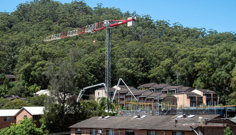 Concrete Boom Pump delivering material to new building site with bushland backdrop. Gosford, Australia. February 26, 2021. 56-58 Beane St. Part of a series.