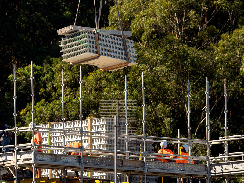 Workmen loading and working PVC Wall formwork on new social housing home unit block at 56-58 Beane St. Gosford, Australia. March 26, 2021. Part of a series.