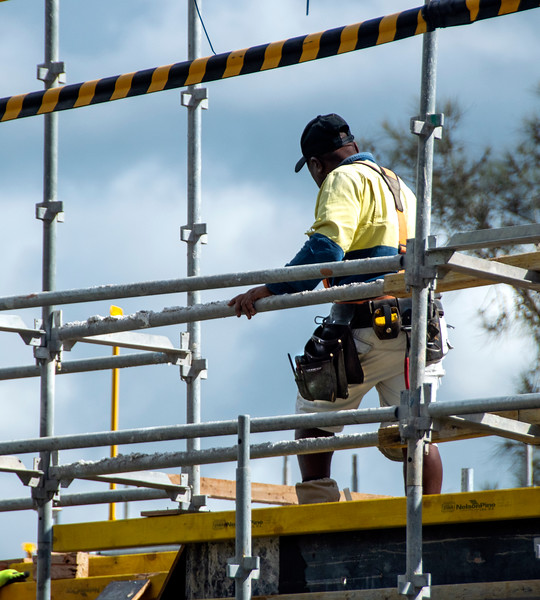 Worker assembling floor formwork on new social housing home unit block at 56-58 Beane St. Gosford, Australia. March 7, 2021. Part of a series.