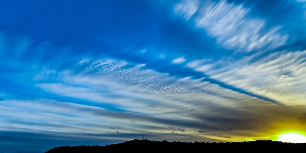 Magnificent white Cirrostratus cloud in blue and gold sky.