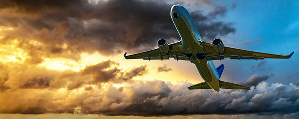 Jet Airliner Flying in a yellow coloured cumulus cloudy sky.