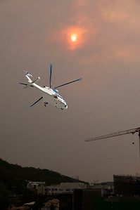 Bushfire sunset sky with an airborne helicopter in the foreground. Sun glow over Gosford city through wildfire smoke and haze. Australia. 2019