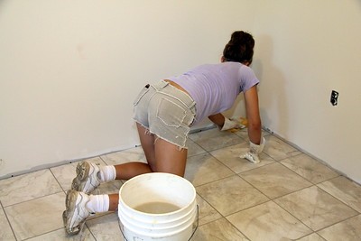 Michelle wiping excess grout from tiles
