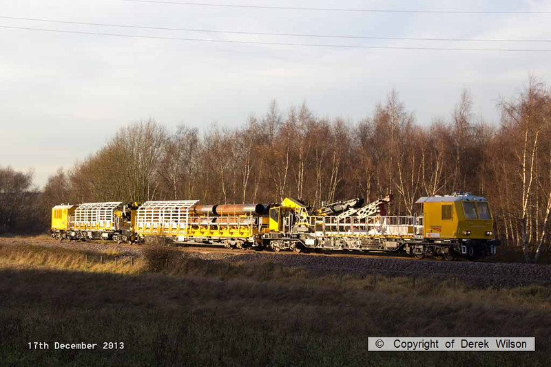 131217-032    Some of the HOPS piling consist, seen at Ollerton pit tip wood on the High Marnham Test Track, nearest is MPV no 99 70 9131 005-9, followed by pile carrying wagon no 006-2, and finally MPV no 003-4. This pile carrying wagon has been numbered wrong, one of the MPV's in the concrete batching consist is 006-7, this wagon should be 002-6.